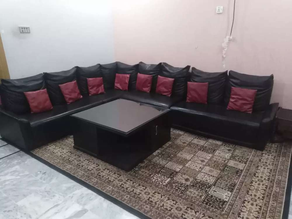 L shaped leather sofa with cushions and center table with storage