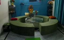 Round shape sofa in green color with center table
