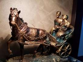 Beautiful sculpture of couple sitting on horse cart