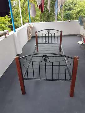 Steel cot with wooden leg.