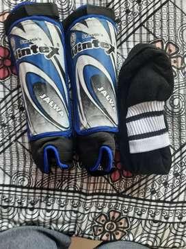 Leg guards and one pair of knee length lycra plain socks for football