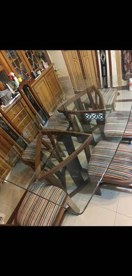 Beautiful glass table with 6 wooden and carved chairs