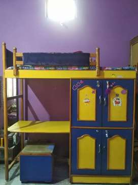 Children's bed with cupboards and a study table with sliding stool