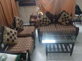 Sofa set with cushions along with glass top wooden table