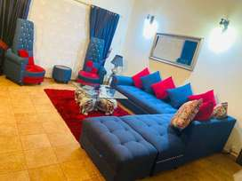 L shape sofa with two coffee chairs, table, lamp, rug and curtain