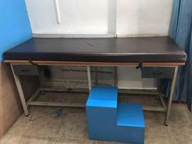 Medical examination table with foot step