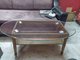 Wooden tea table with spherical glass top and lower rack.