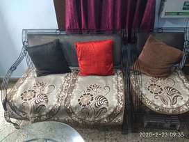 A wrought iron made sofa set with oval shape center table.