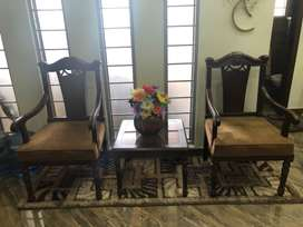 Two chairs with wooden back and one wooden table set