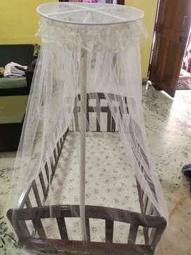 Babyhug Ionia wooden cradle with mosquito net and movable wheels