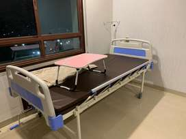 Hospital bed with air mattress, drip stand and foldable table