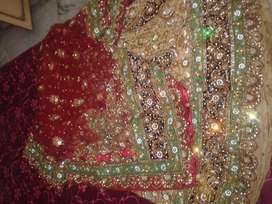 Very heavy work bridal lehenga in golden color and red net dupatta