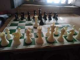 Tournament chess mat with pieces.