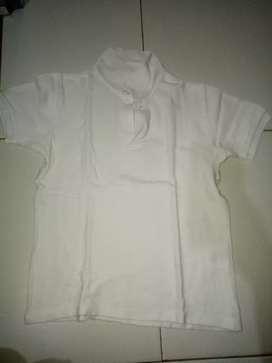 Baju kaos berkerah warna putih.