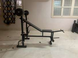 Gym bench with 3 way fold also with a barbell.