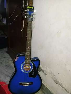 Blue colour guitar with a packt of guitar strings
