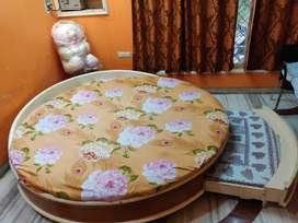 Wooden bed with a mattress and small bed attached with it.