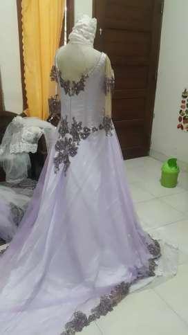 Baju pengantin warna ungu cerah.