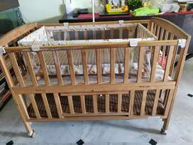 Wooden baby cot with cradle and mosquito net